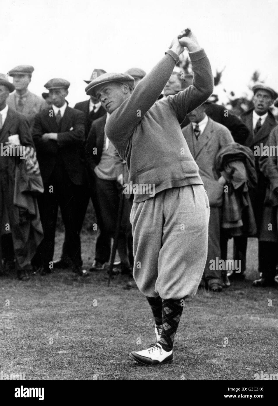 Golfer watched by spectators.      Date: circa 1920s - Stock Image