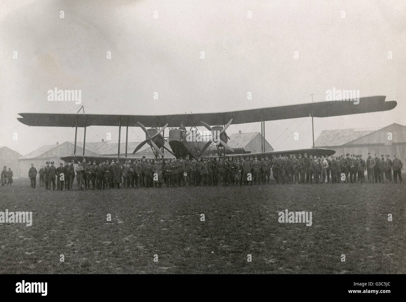 Handley Page biplane, O/400 bomber, with a large group of men standing in front of it on an airfield.      Date: Stock Photo