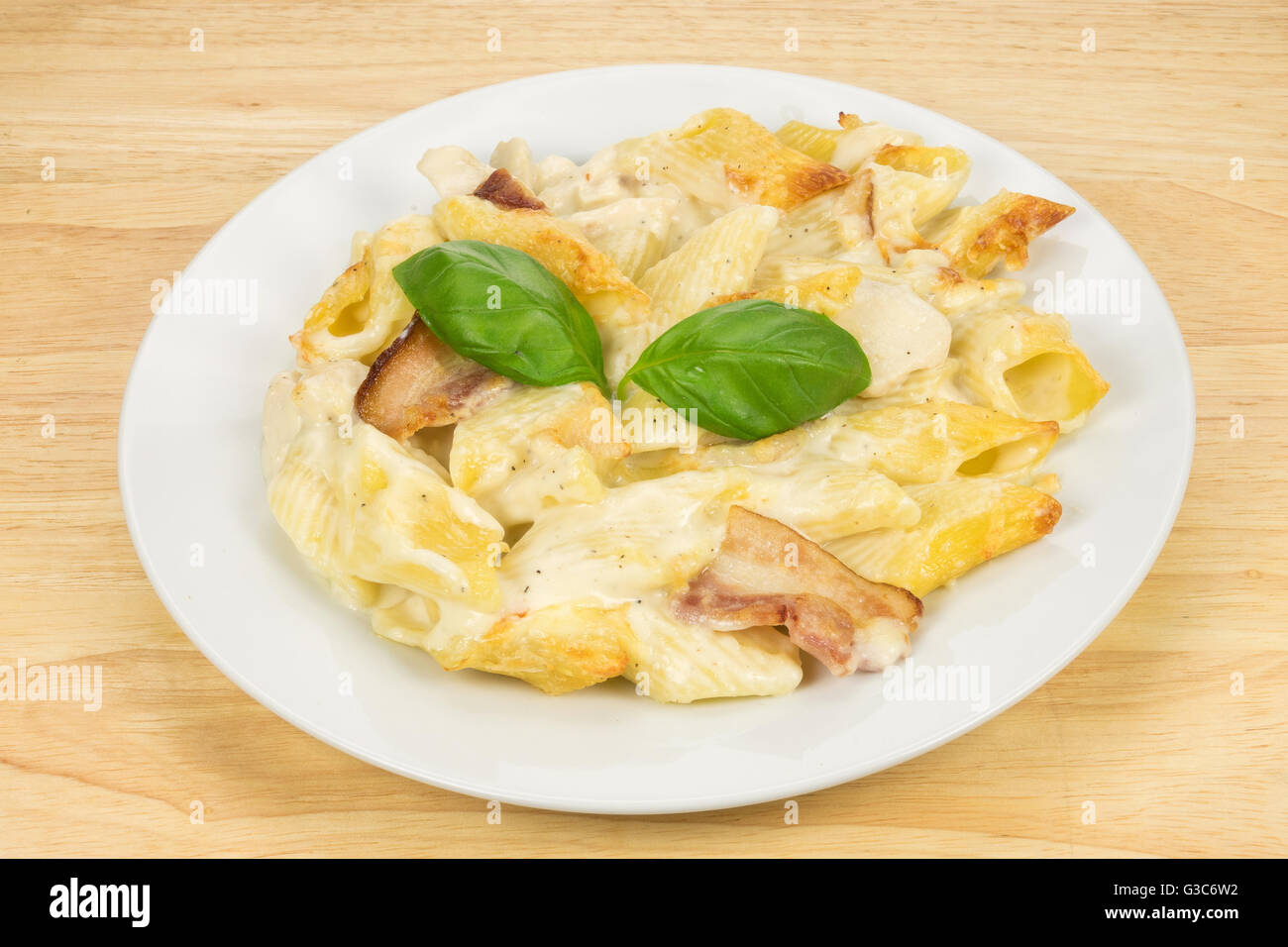 Chicken and bacon pasta bake meal served on a white plate - Stock Image