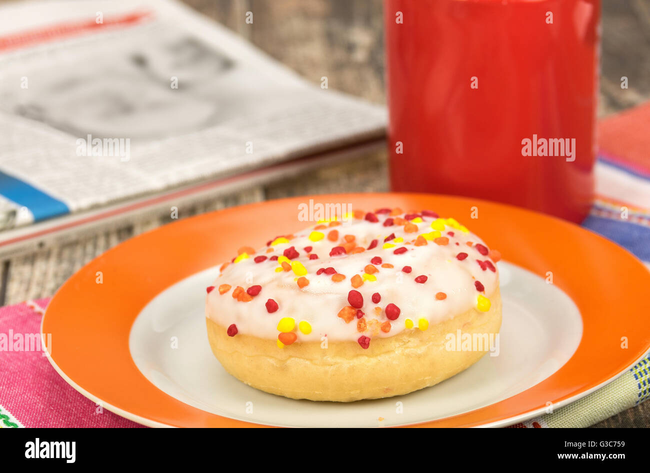 Fresh frosted donut snack with a hot drink - Stock Image
