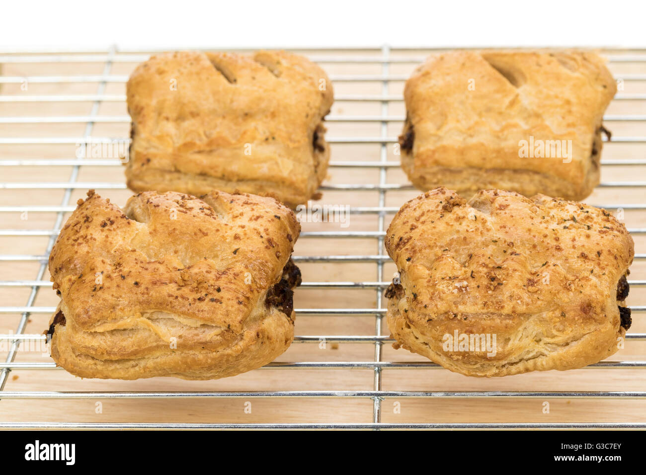 Close-up of hot sausage rolls cooling on a wire rack - Stock Image