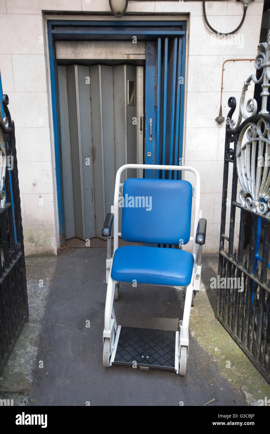 National Health Service patient chair left outside  back entrance of London hospital, UK - Stock Image