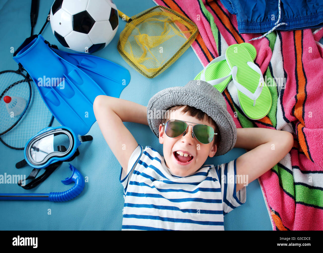 boy with sunglasses and toys on blue background Stock Photo