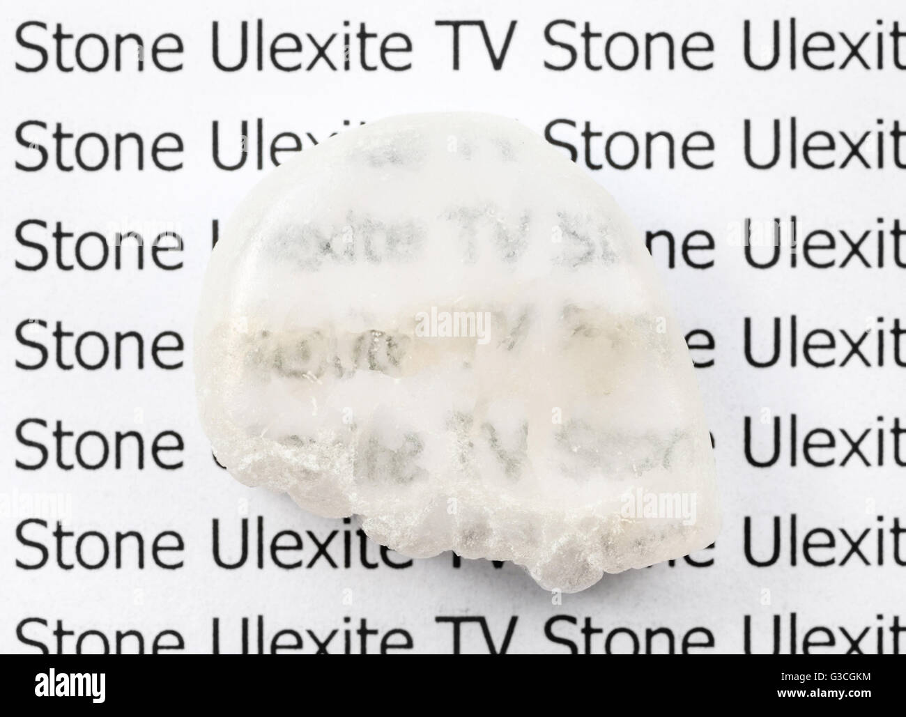 polished Ulexite (TV stone) natural mineral gemstone on sheet of paper with letter. Ulexite is known as TV rock - Stock Image