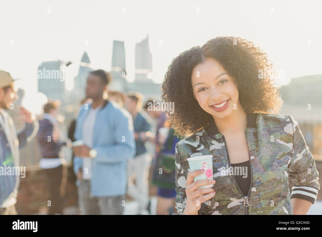 Portrait smiling young woman drinking cocktail at rooftop party - Stock Image