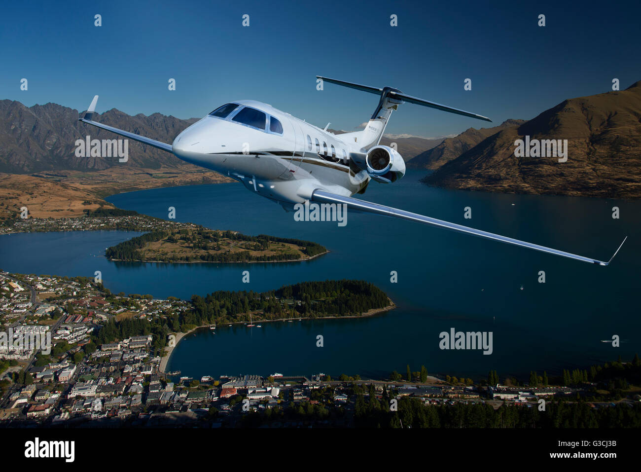 An Embraer Phenom 300A light business jet climbs to altitude on a flight mission. - Stock Image