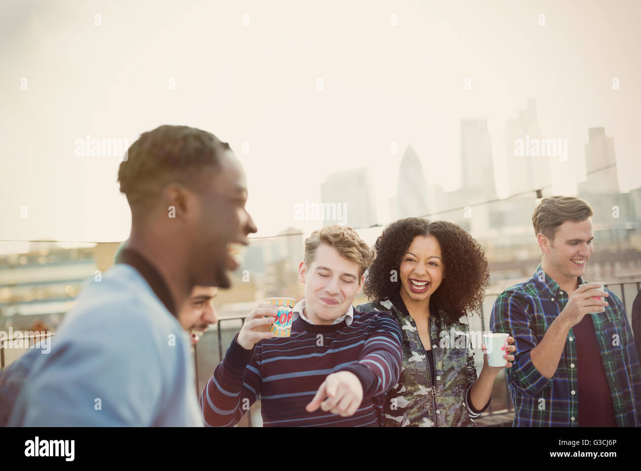 Young adult friends drinking and laughing at rooftop party - Stock Image