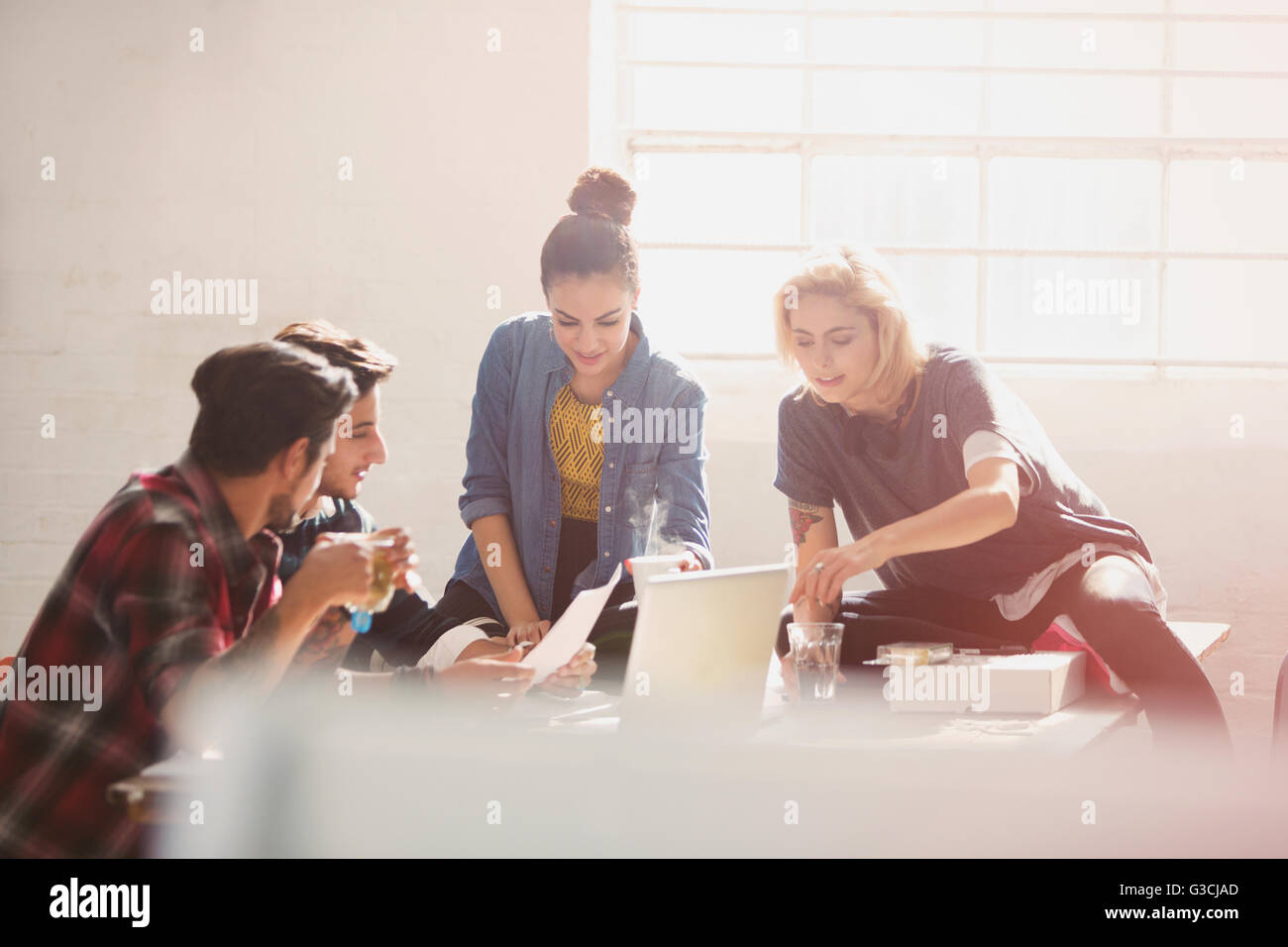 Creative young business people brainstorming at laptop in sunny office - Stock Image