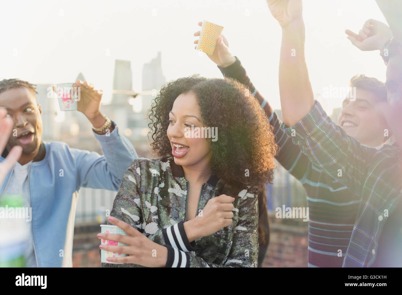 Young woman dancing and drinking at rooftop party - Stock Image
