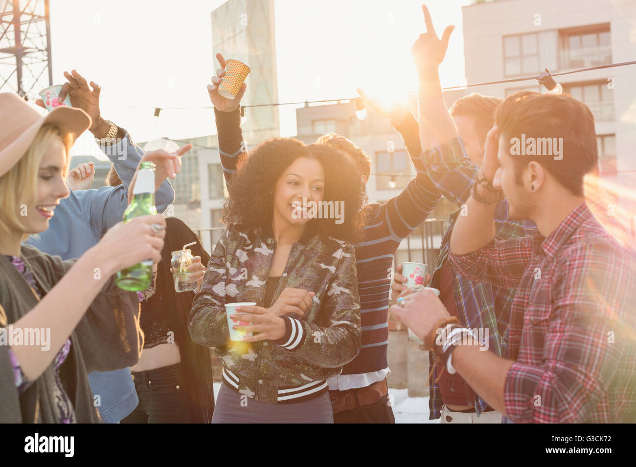 Enthusiastic young adult friends dancing and drinking at rooftop party - Stock Image