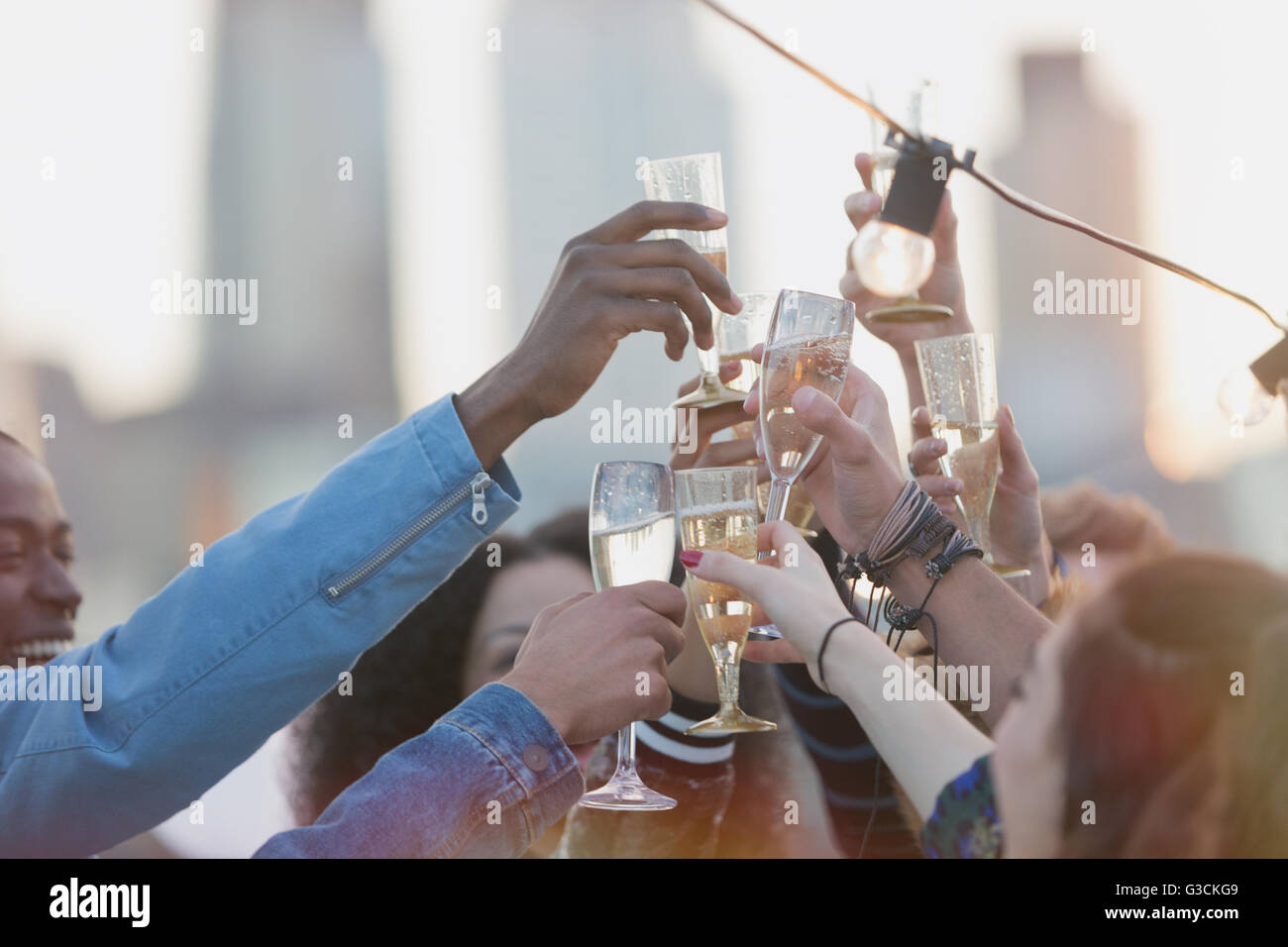 Young adult friends toasting champagne flutes at party - Stock Image