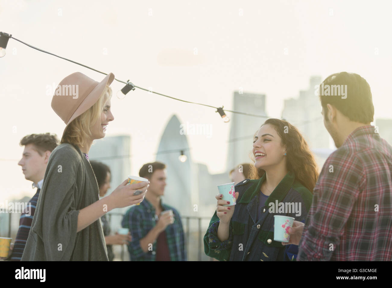 Young adult friends drinking and talking at rooftop party - Stock Image