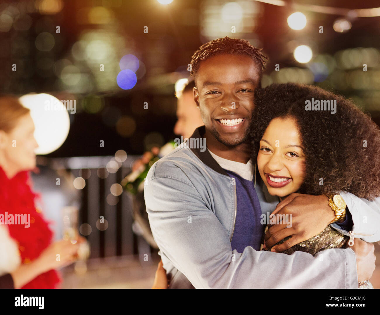 Portrait smiling young couple hugging at party - Stock Image