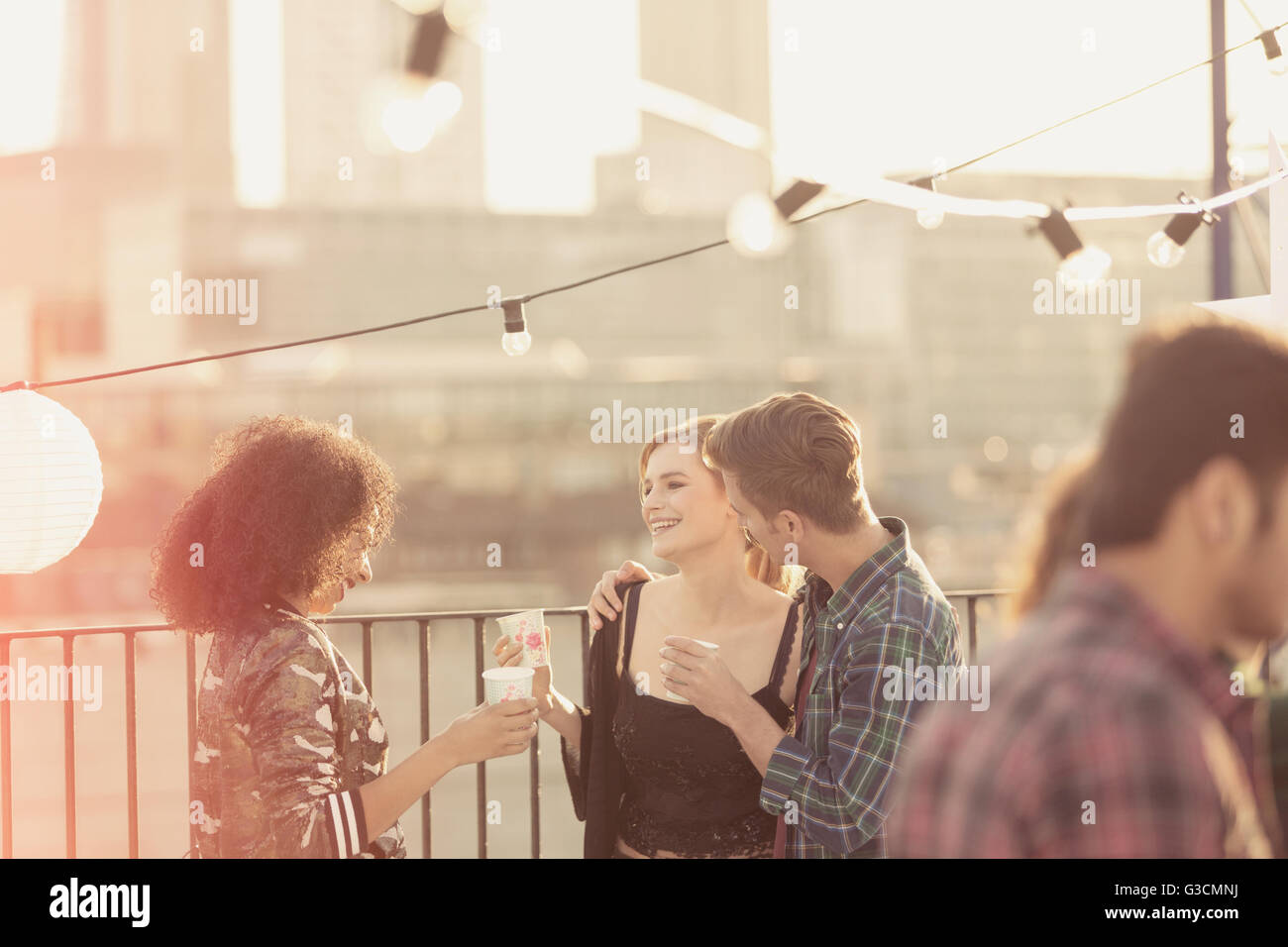Young adult friends talking and drinking at rooftop party - Stock Image
