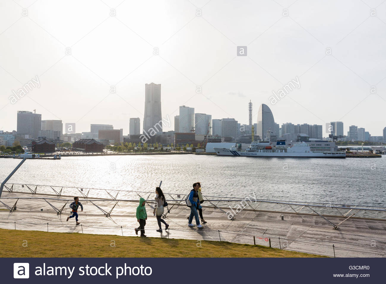 People strolling on promenade of the Osanbashi pier for seagoing vessels in front of Yokohama city silhouette, Yokohama, - Stock Image