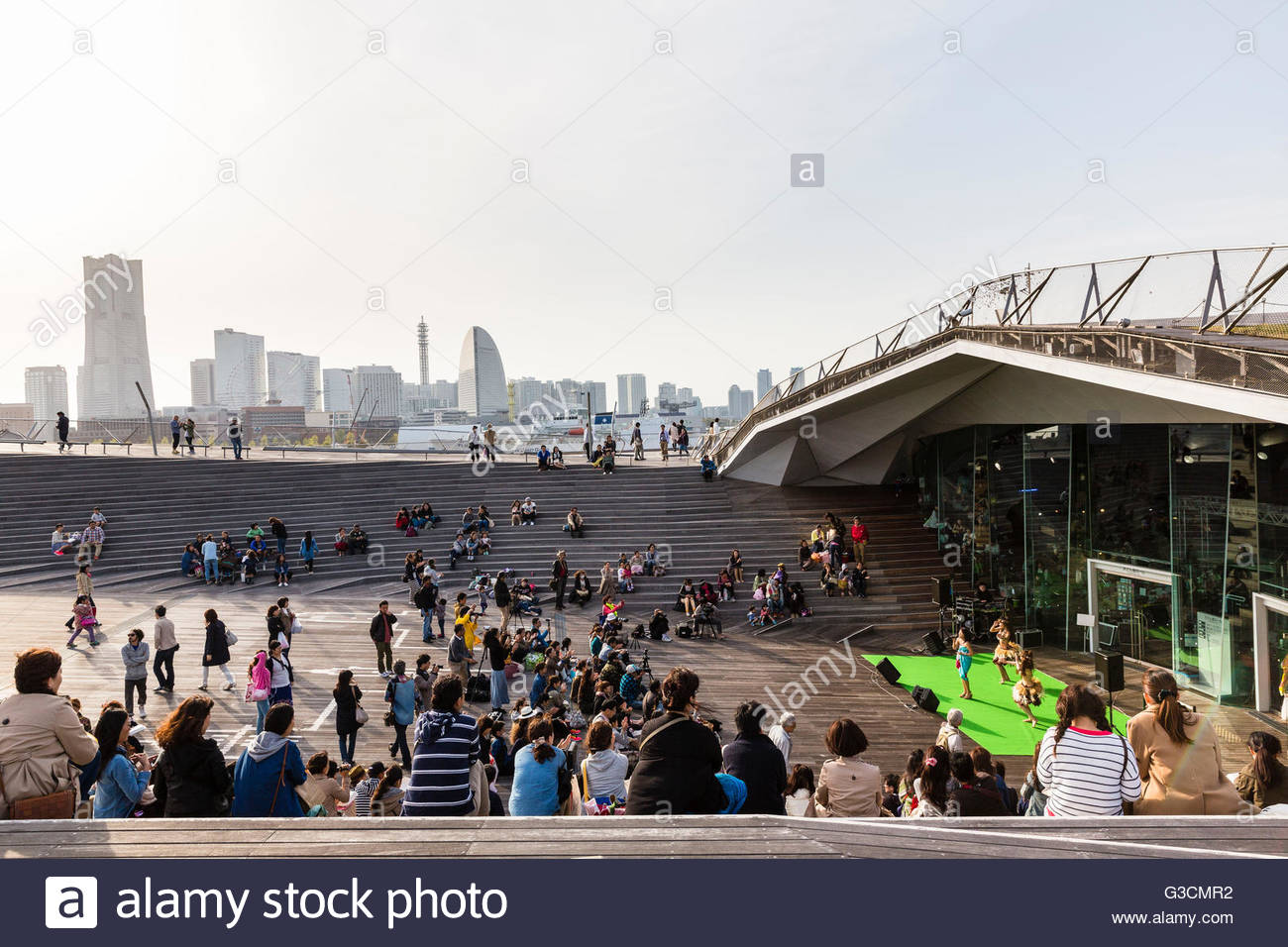Spectators at a stage at the Osanbashi Pier for seagoing vessels in front of Yokohama city silhouette, Yokohama, - Stock Image