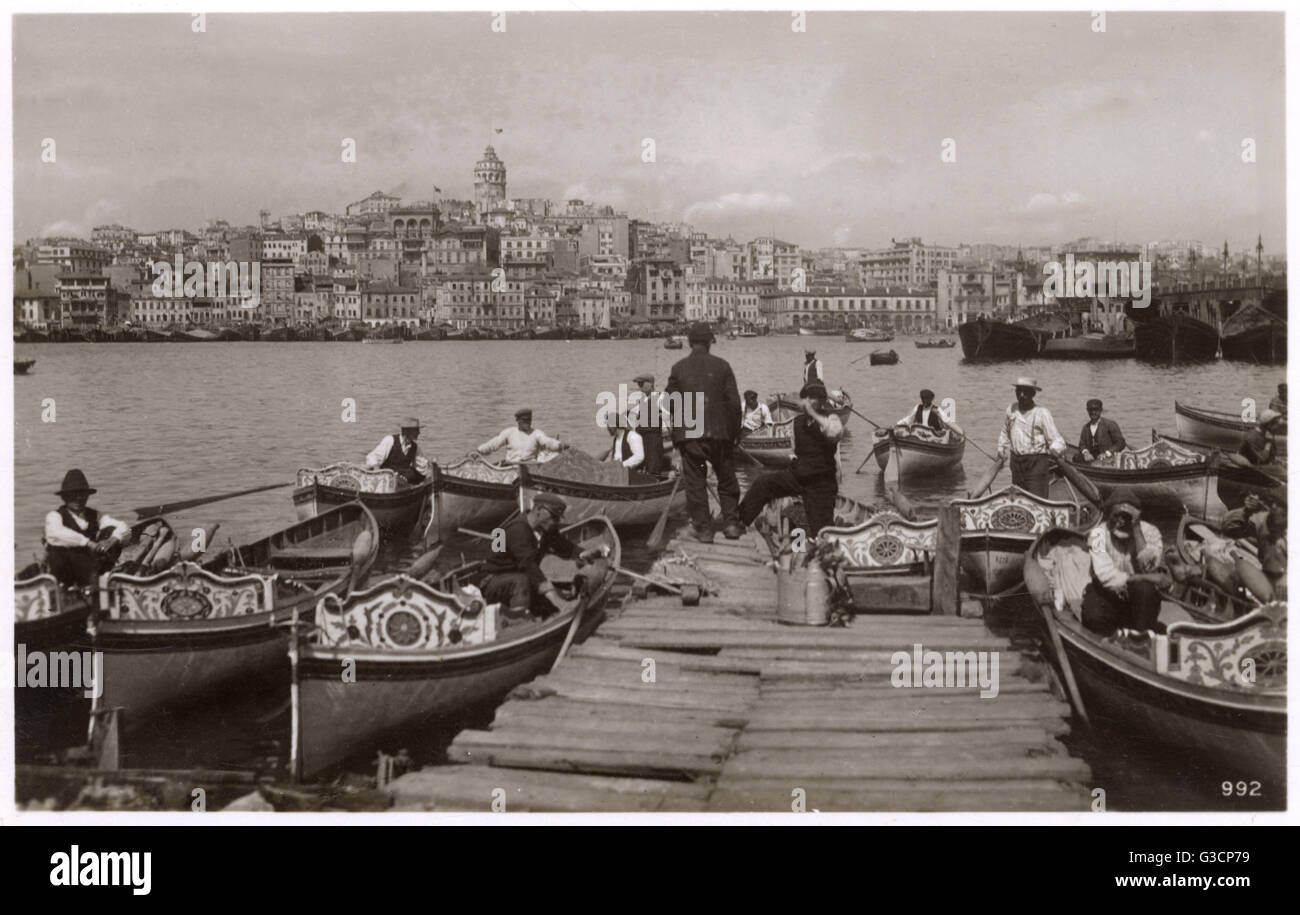 Ferryboats and boatmen moored close to the Bridge and Quay at Galata, Constantinople, Turkey, ready to provide transport - Stock Image