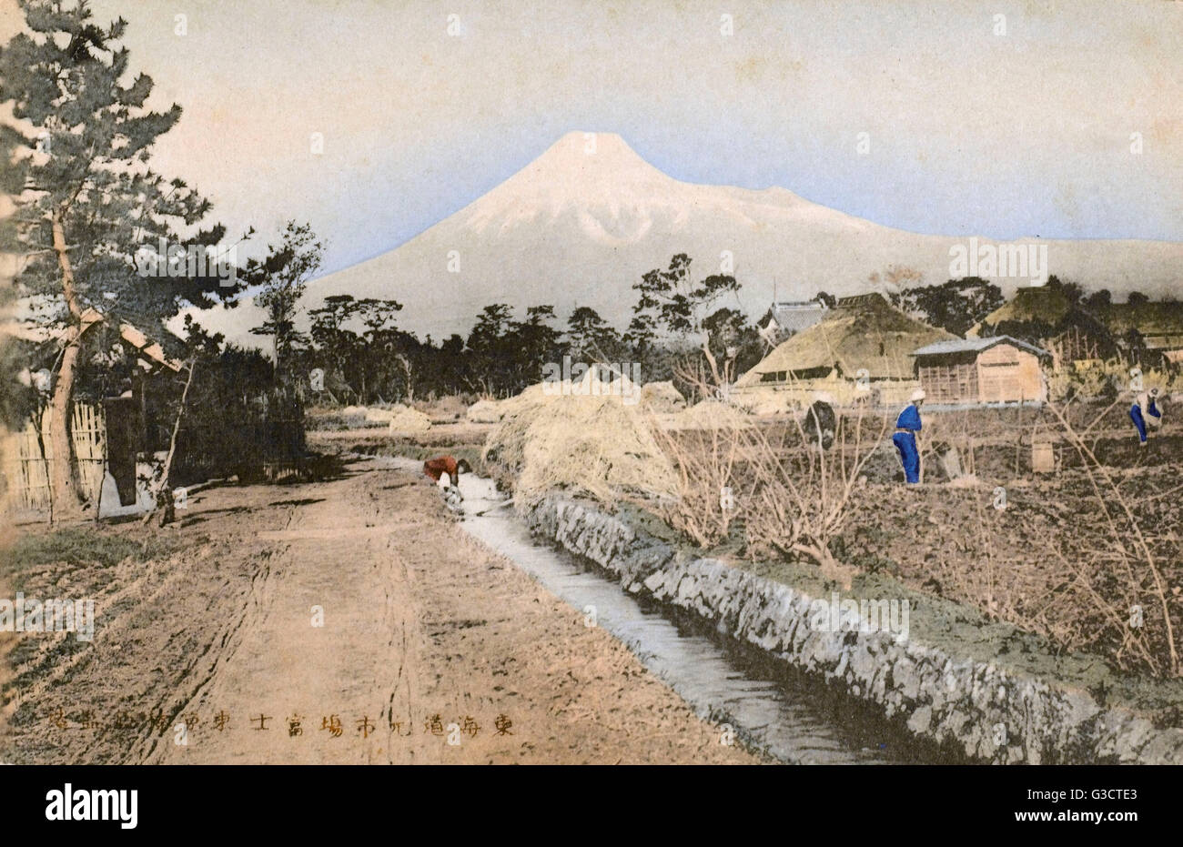 Mount Fuji, Japan - with a village and agricultural workers labouring in the fields in the foreground.     Date: - Stock Image