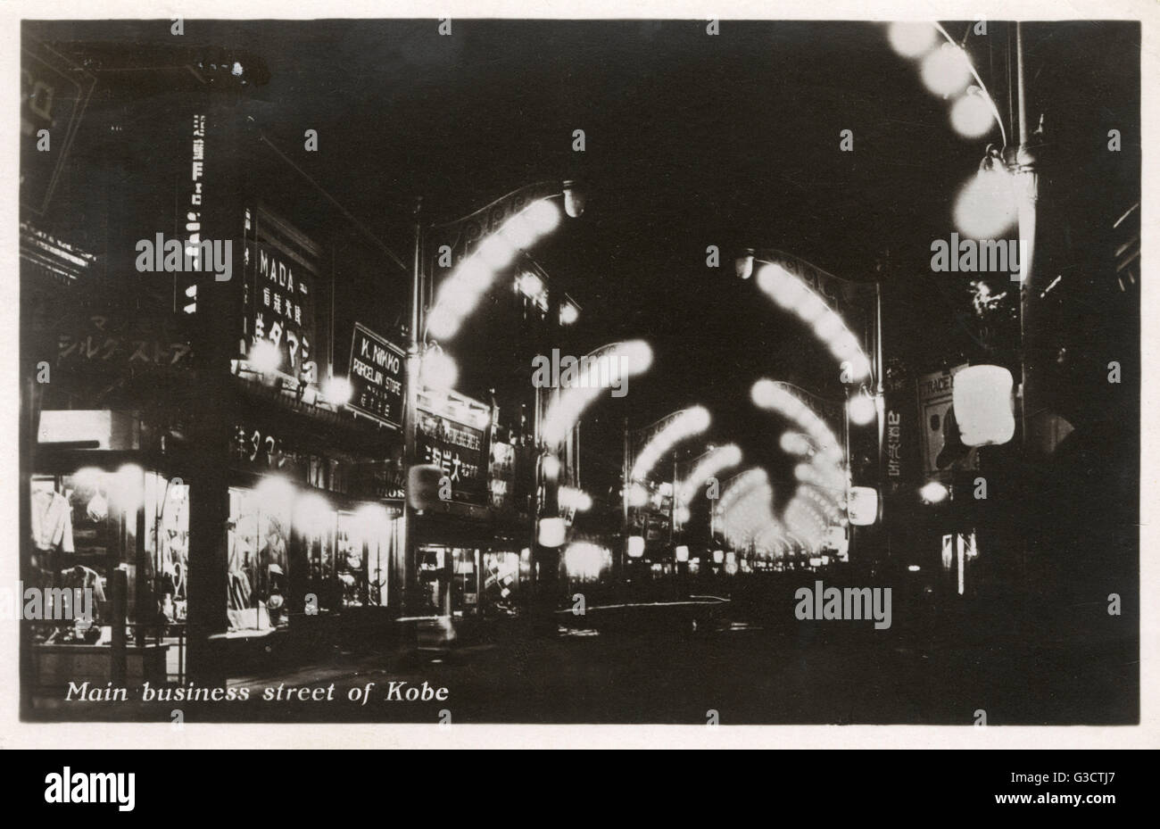 Kobe, Japan - Nightime view of the main business street showing attractive arrays of street lighting     Date: 1935 - Stock Image