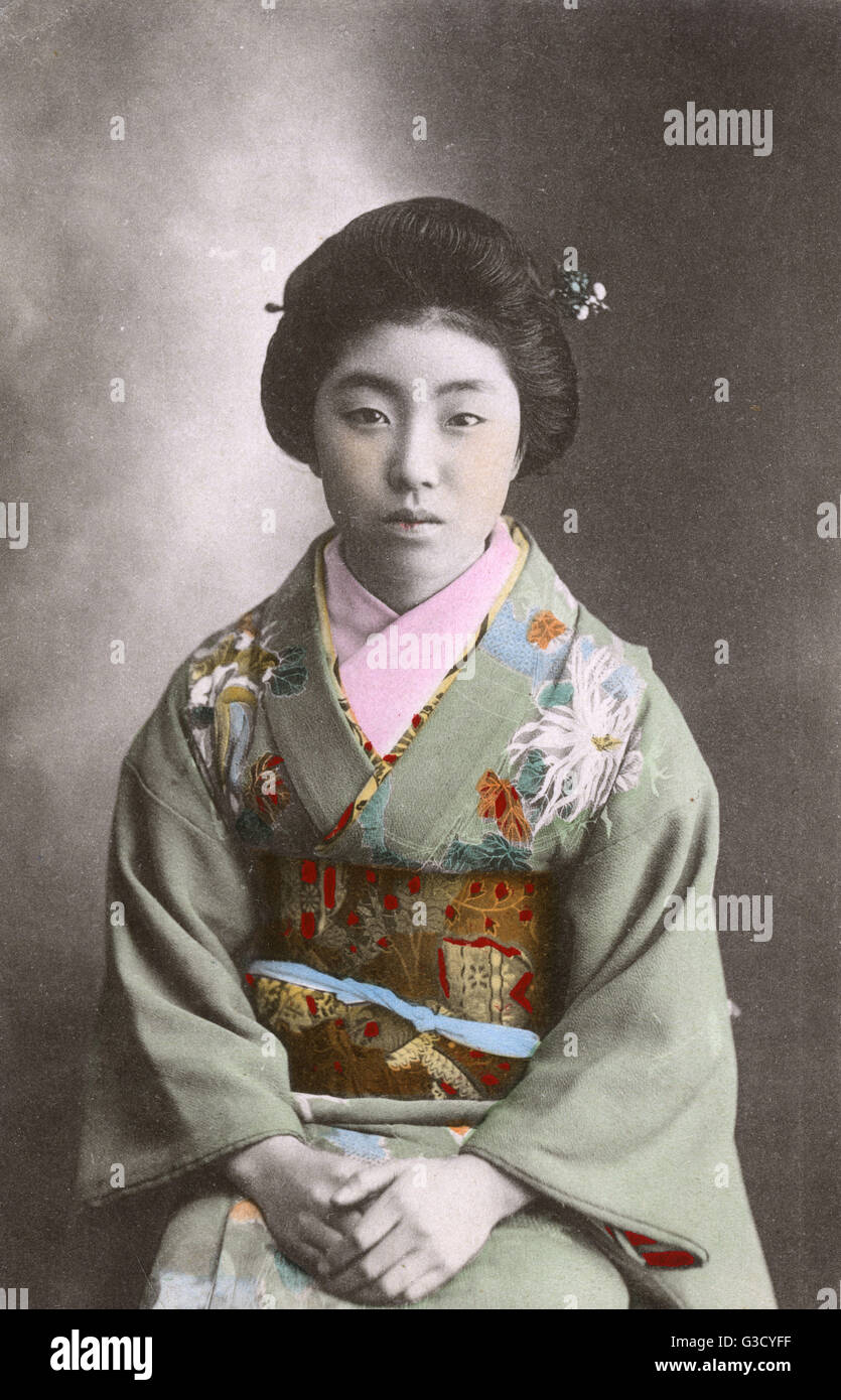 A Japanese Geisha girl - classical portrait photograph wearing a beautifully-decorated silk kimono.     Date: 1910s - Stock Image