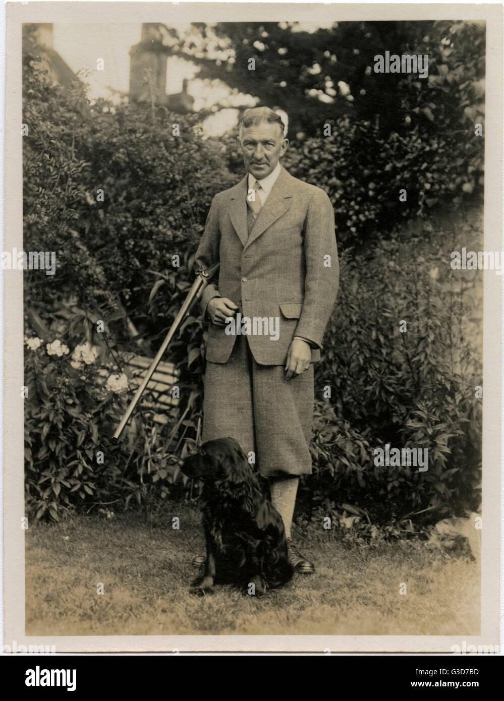 Man with gun and retriever dog in a garden.      Date: circa 1930s - Stock Image