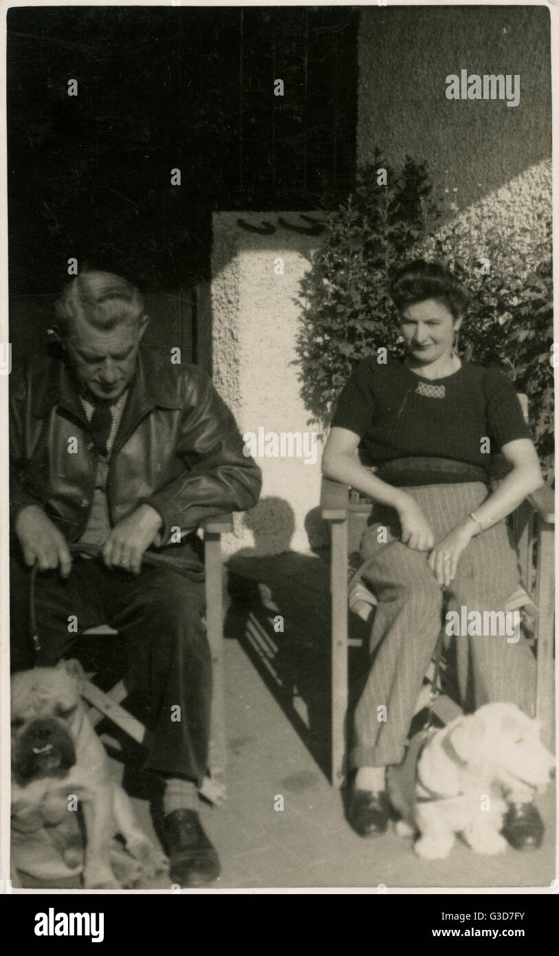 Couple in garden chairs with two dogs.      Date: circa 1930s - Stock Image