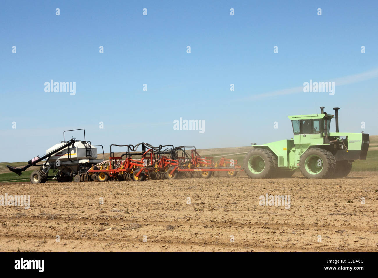 A farmer seeding a field using a Steiger Bearcat tractor pulling an Bourgault Air Hoe Drill and Air Seeder. In Alberta - Stock Image