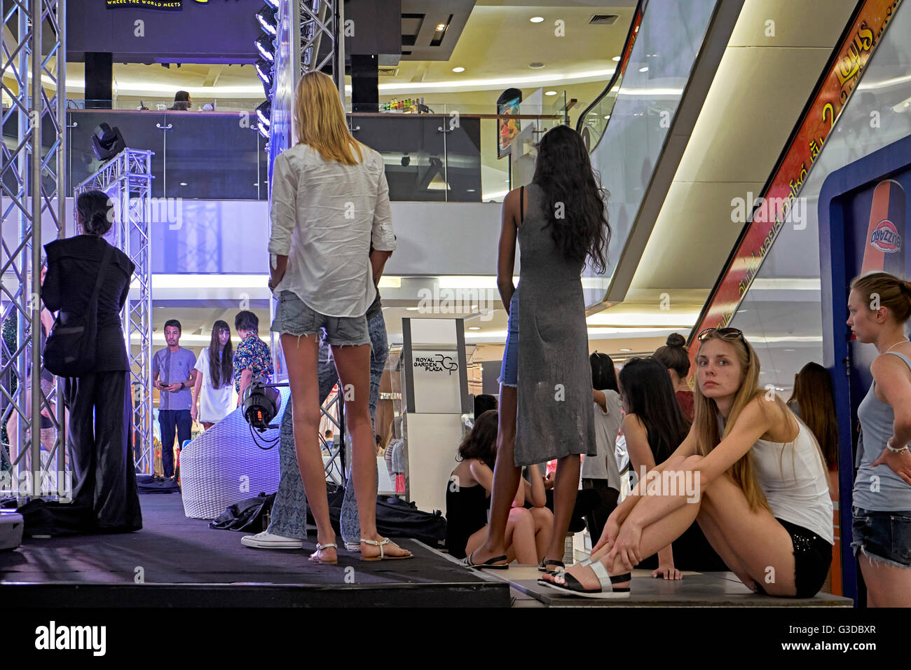 Female models backstage at a fashion show practice run. - Stock Image