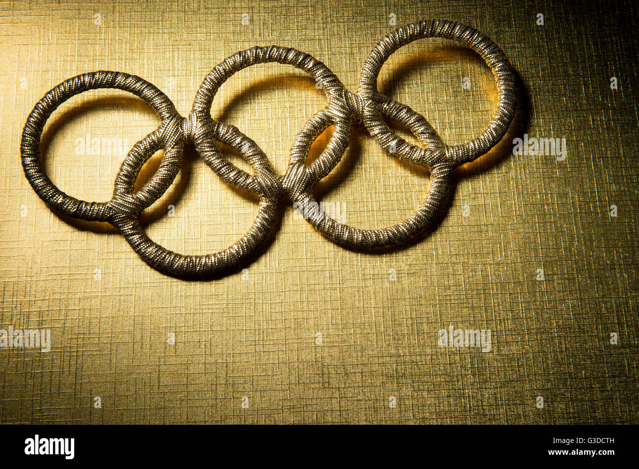 RIO DE JANEIRO - FEBRUARY 3, 2016: Gold Olympic rings sit spotlit on shiny golden background as a symbol of the - Stock Image
