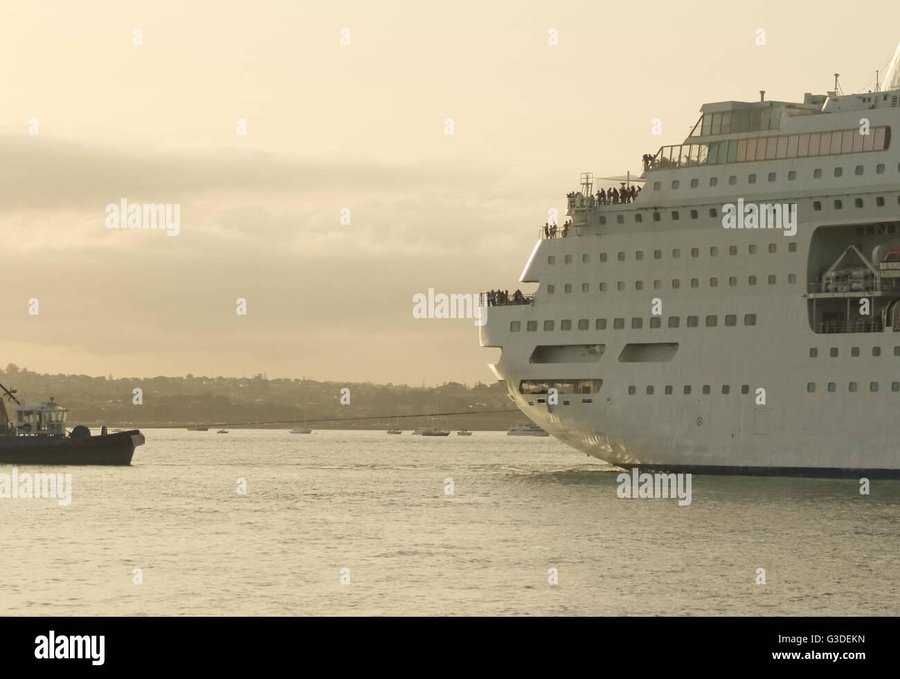 Tugboat pulling a large cruise ship - Stock Image