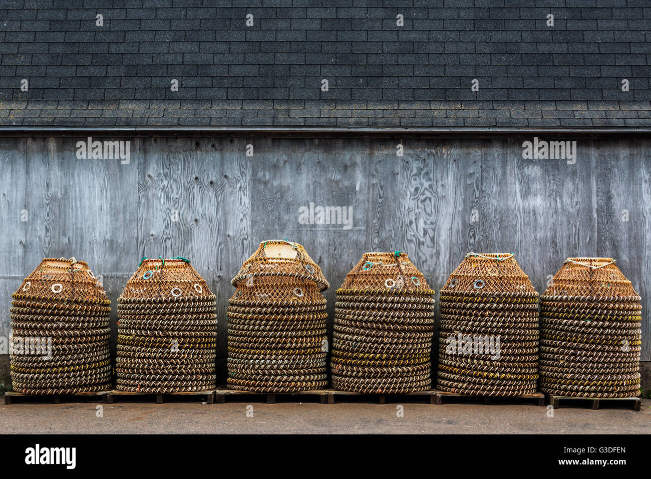 Crab pots for the commercial crab fishery stacked up on a wharf in rural Prince Edward Island, Canada. - Stock Image