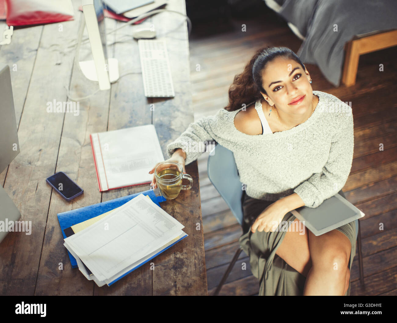 Portrait confident college student studying with tea and digital tablet Stock Photo