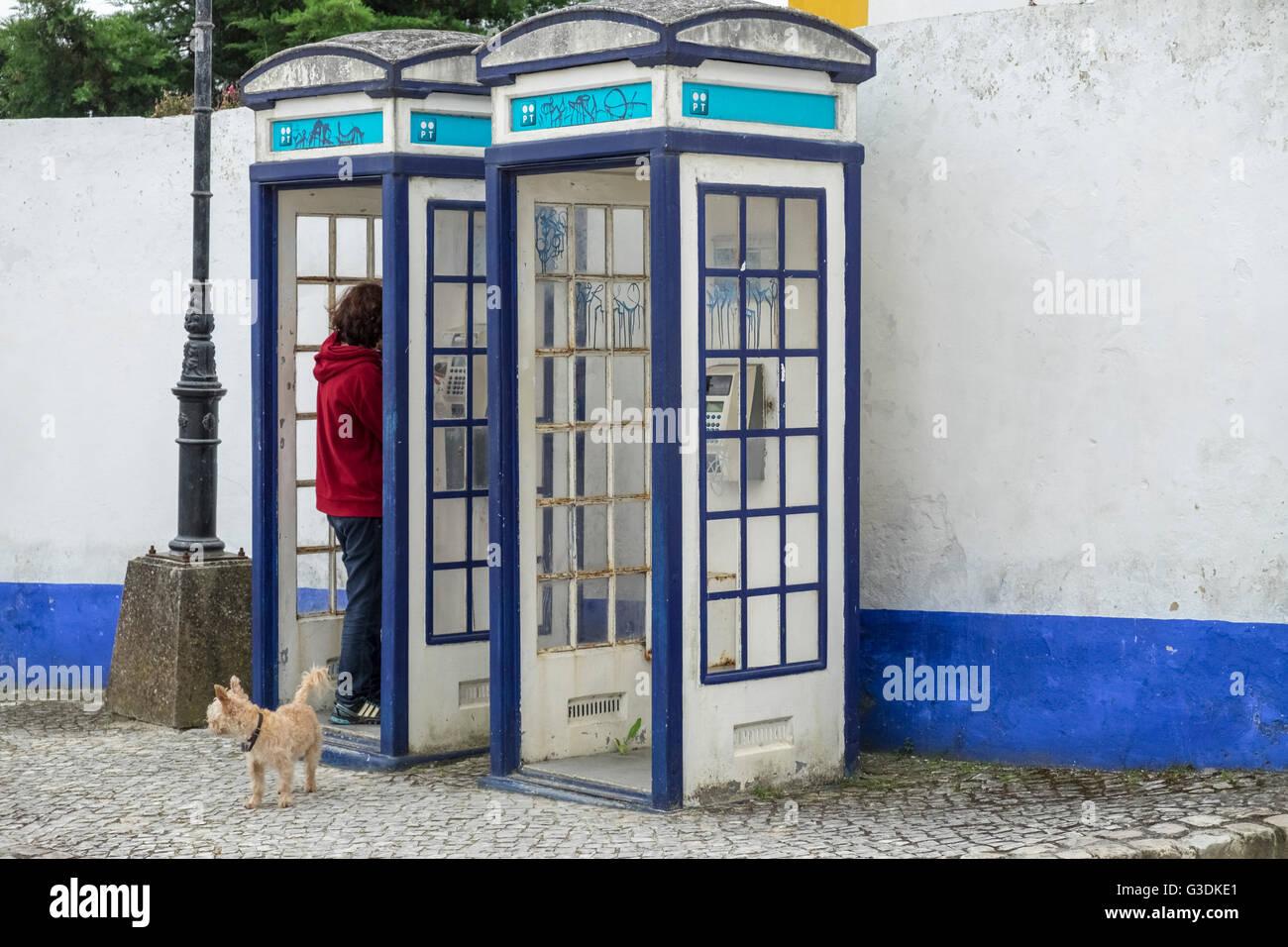 Woman using old style landline telephone box, Obidos, Estremadura, Portugal - Stock Image