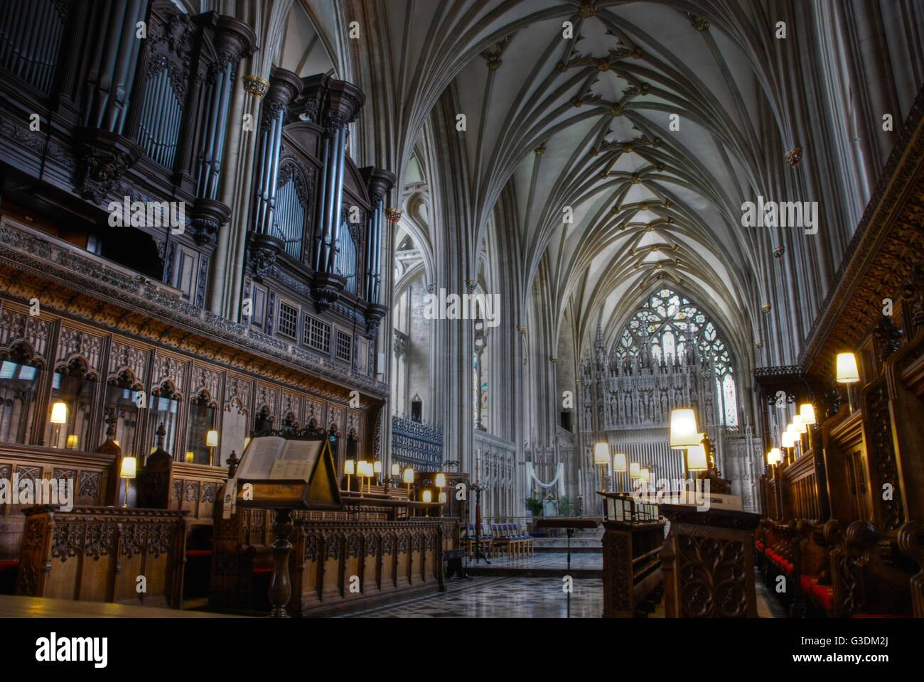 Interior shot of Bristol cathedral showing vaulting over the seating for the choir and organ pipes. - Stock Image