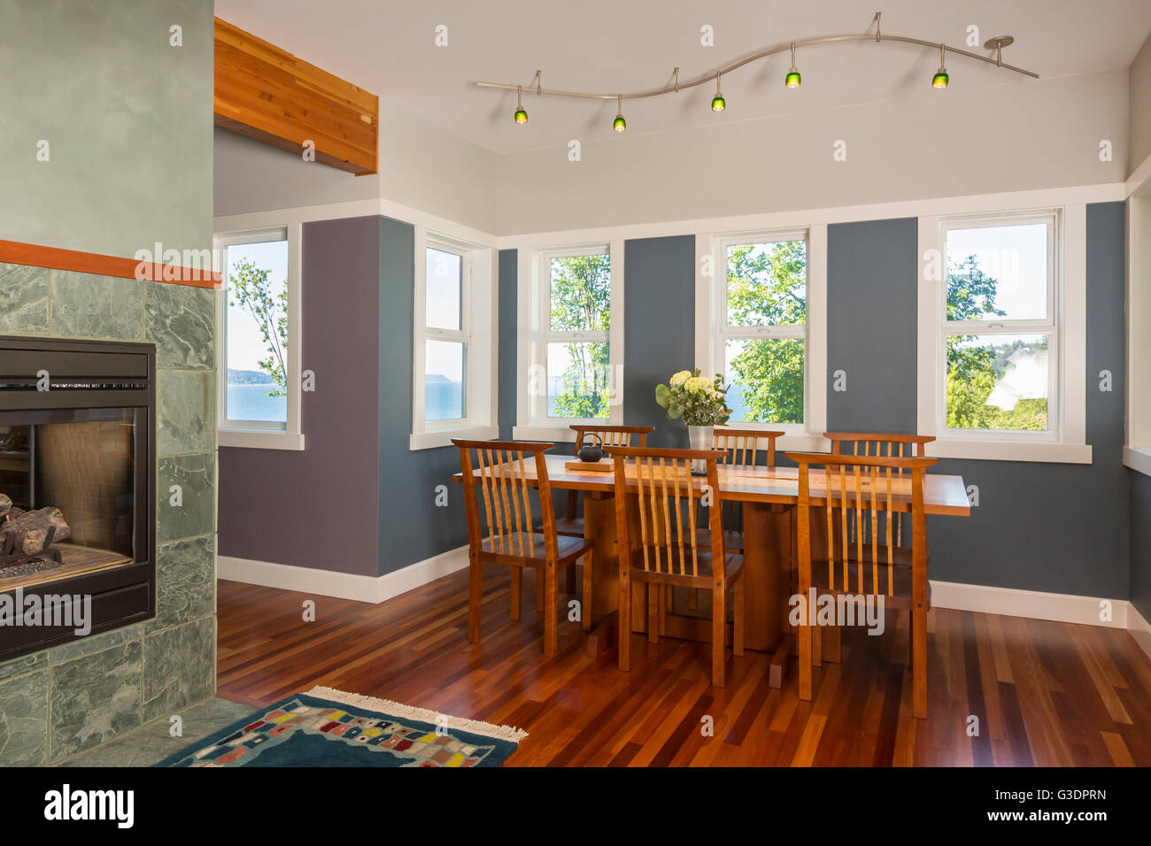 Dining area table & chairs with wood floors, painted walls, accent lighting & view windows in contemporary - Stock Image