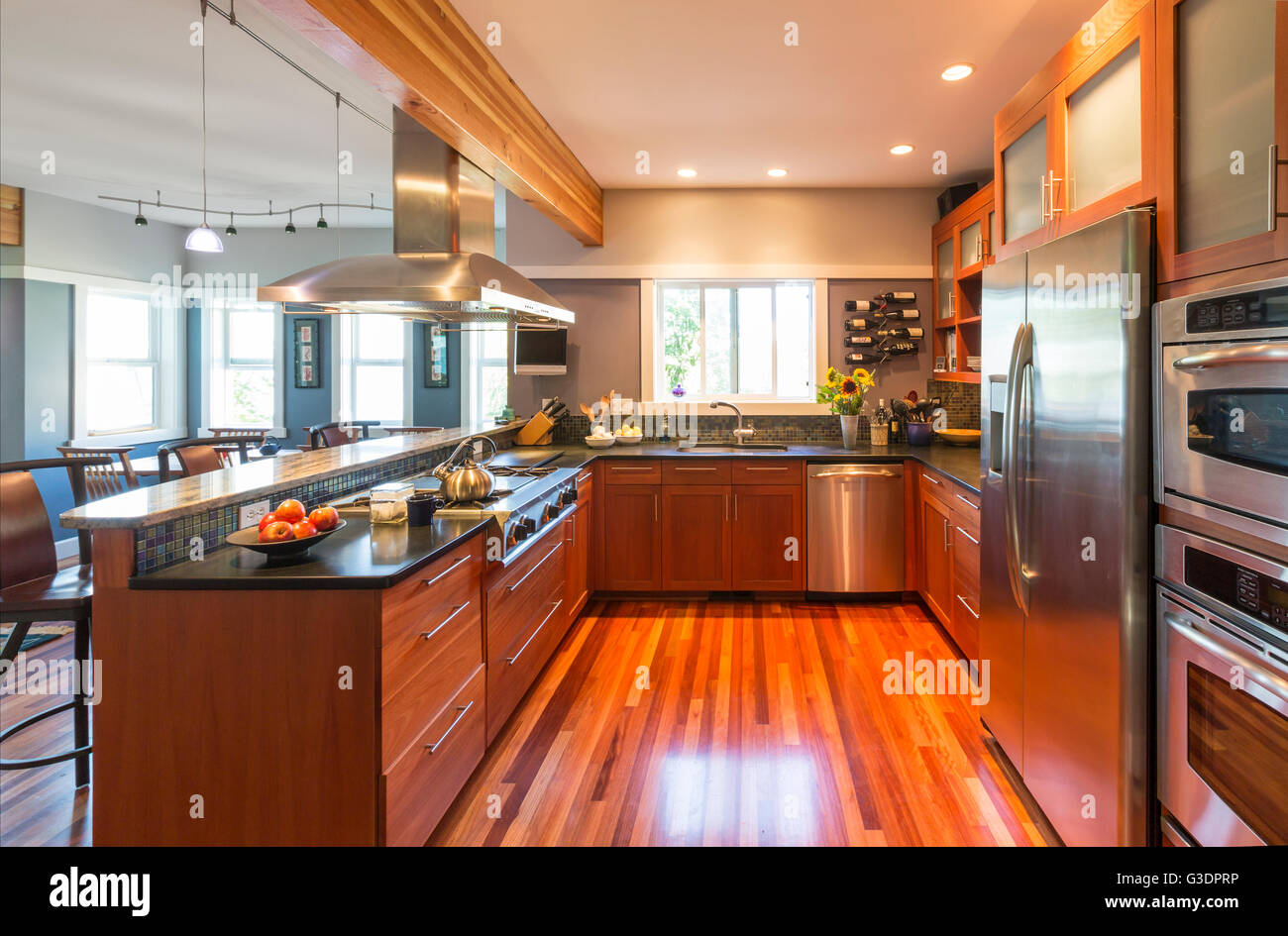 Spacious, contemporary upscale home kitchen interior with wood cabinets & floors, accent lighting & stainless - Stock Image