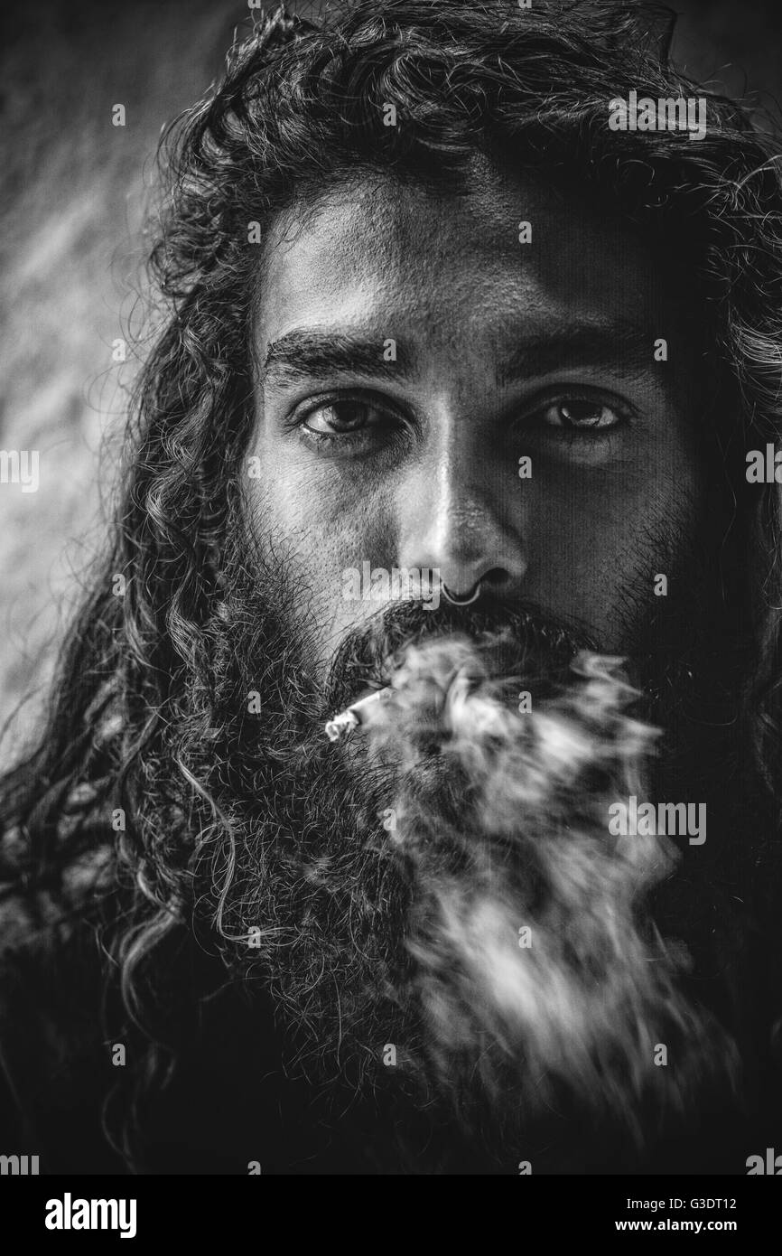 Black and white shot of indian beard man with long hair smoking out