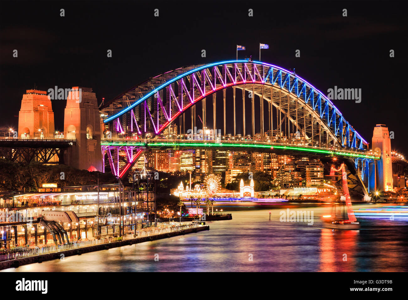 Brightly illuminated arch side of landmark Sydney Harbour Bridge after sunset reflecting lights in blurred still - Stock Image