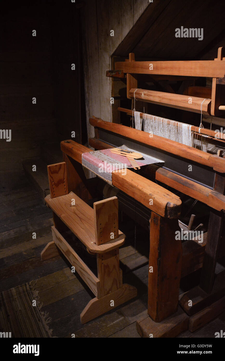 An old loom with a weaving sits dusty and quietly under a spotlight in an old wood floored room - Stock Image