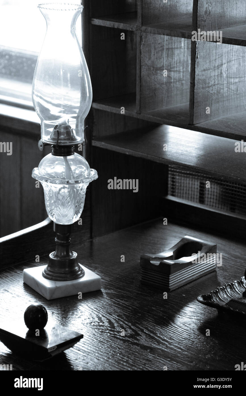 An old writing set including ink well and blotter along with kerosene lamp sit on old wooden desk with pigeon hole - Stock Image