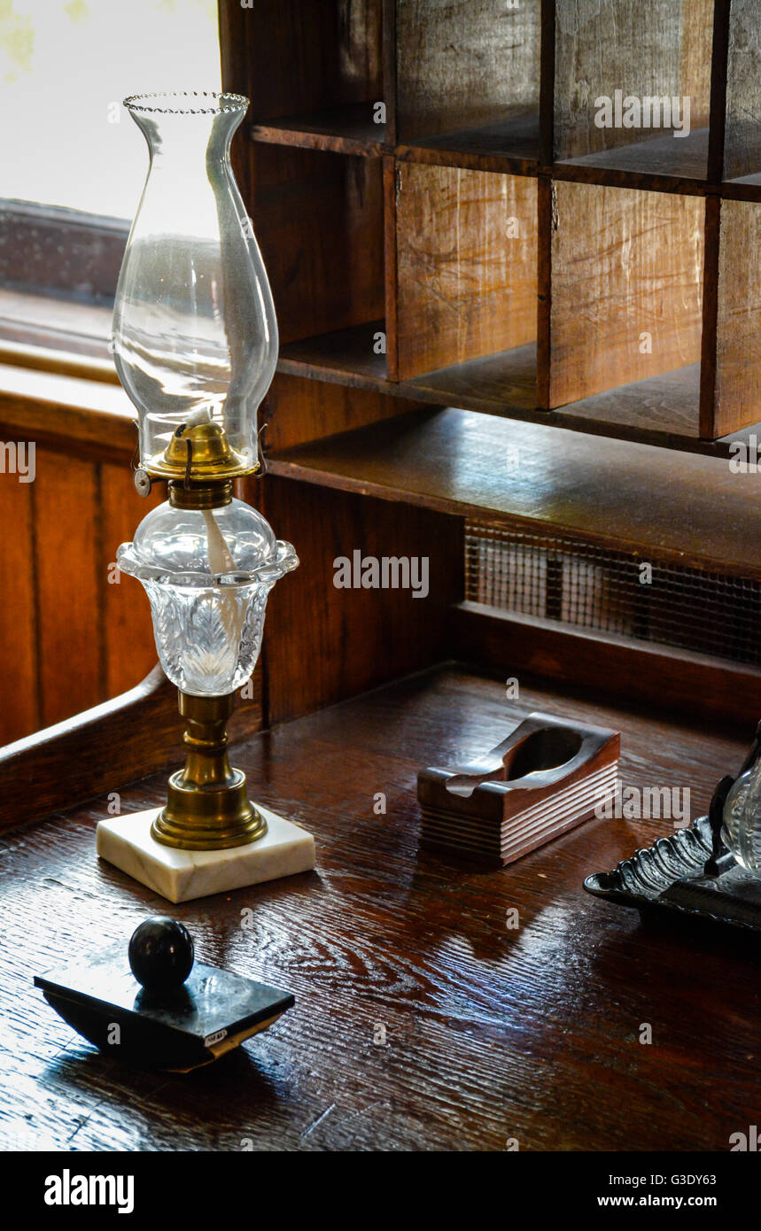 An old writing set including ink well and blotter along with kerosene lamp sit on old wooden desk with pigeon hole Stock Photo