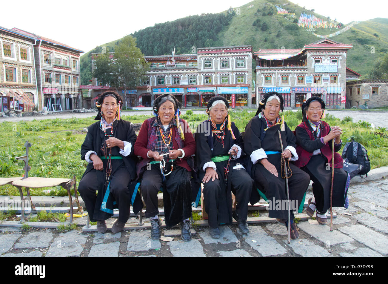 Tibetan women sitting at the main square in Tagong, former Kham region in Sichuan province - Stock Image