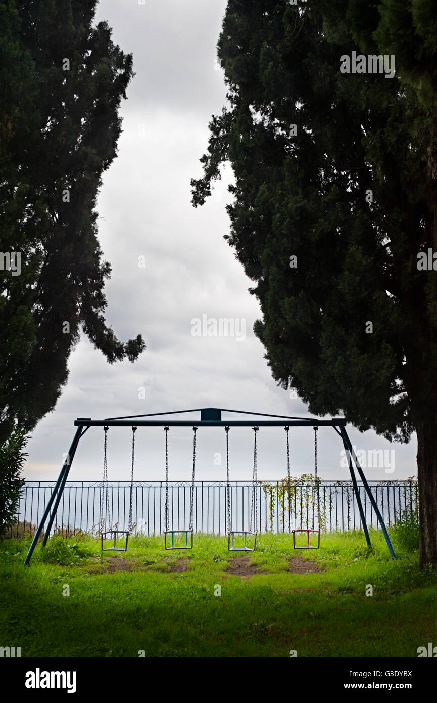 A swing set on a deserted children´s playground - Stock Image