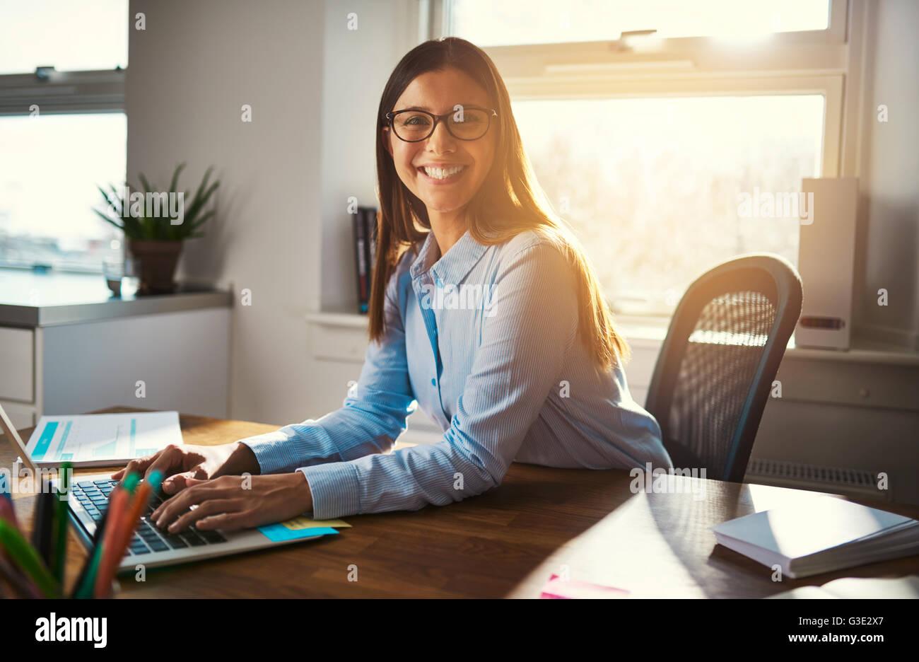 Female entrepreneur at desk smiling at camera, blue warm colors - Stock Image
