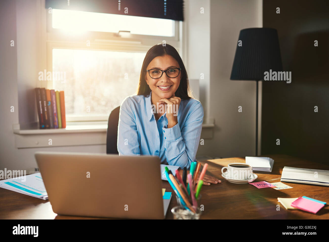 Female entrepreneur sitting at desk smiling at camera - Stock Image
