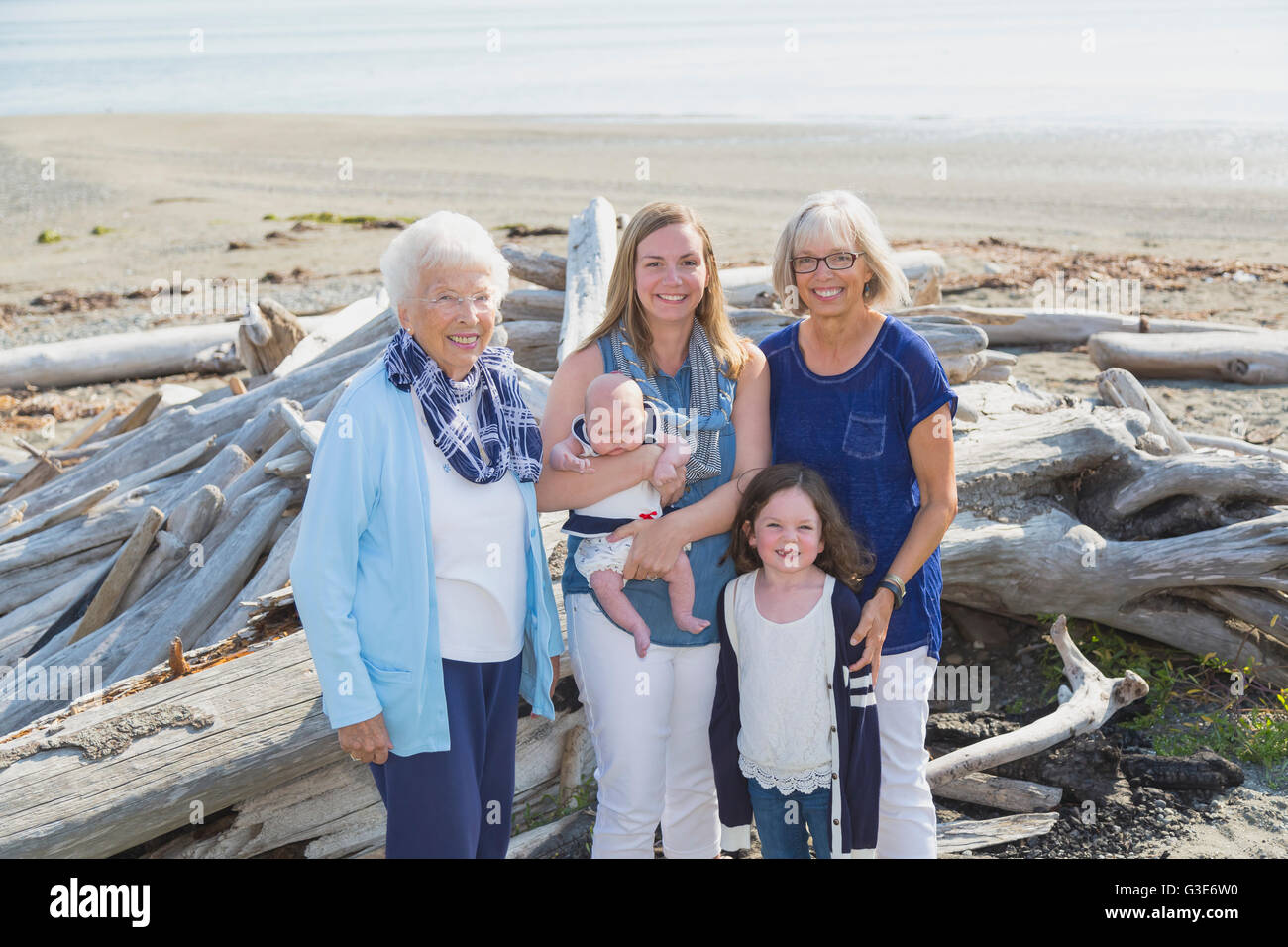 Four generations of women in a family posing on a beach; Fox Spit, Whidbey Island, Washington, United States of Stock Photo