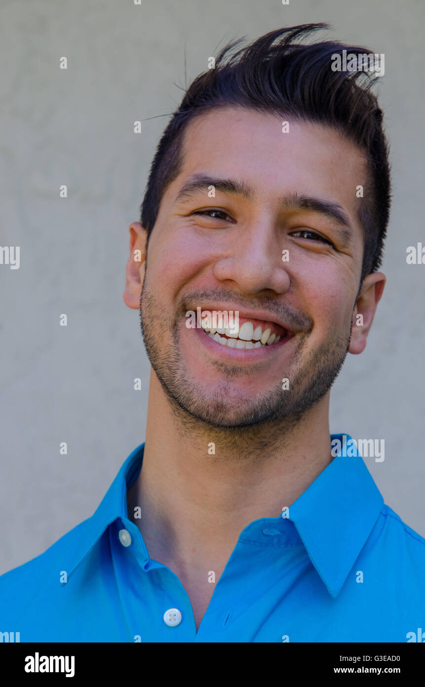 portrait of a handsome young Hispanic man smiling looking very happy - Stock Image
