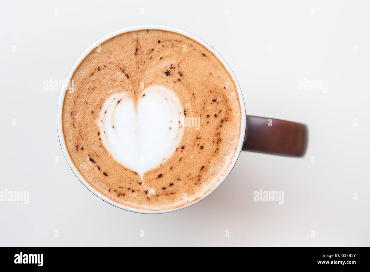 Cup of cappuccino coffee with the milky foam on top in a heart shape viewed from above in a brown cup on white table - Stock Image