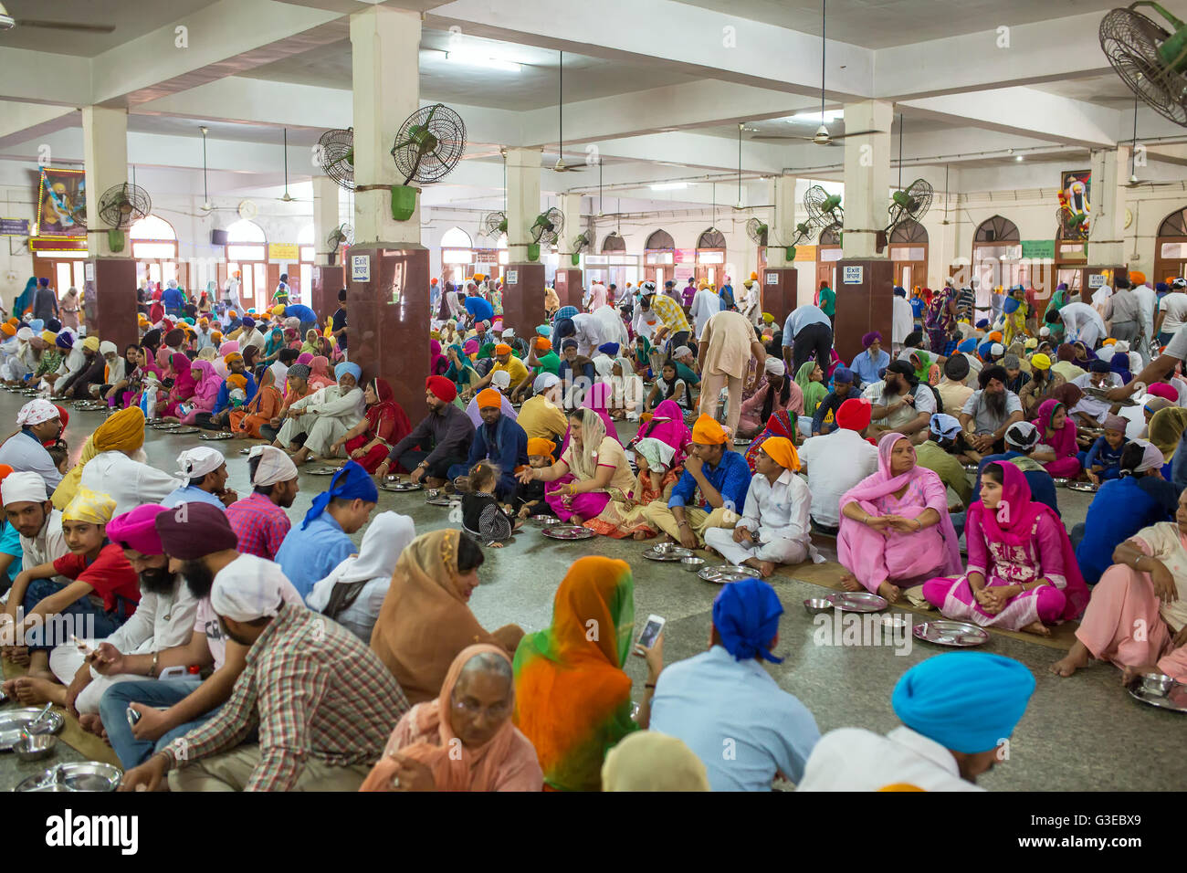 unidentified indian people eating free food in the temple