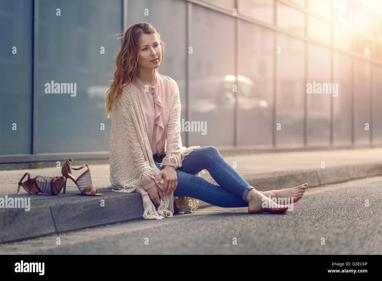 Serious pretty trendy young woman sitting relaxing on a sidewalk on an urban street in her high heels and fashionable - Stock Image